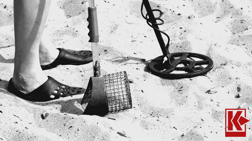 Black and White Image of Person Hunting on the Beach with Metal Detector Coil in the Sand and Sand Scoop with Rusted Basket in Front with Sandy Background and Kellyco K Logo in the Lower Right Corner