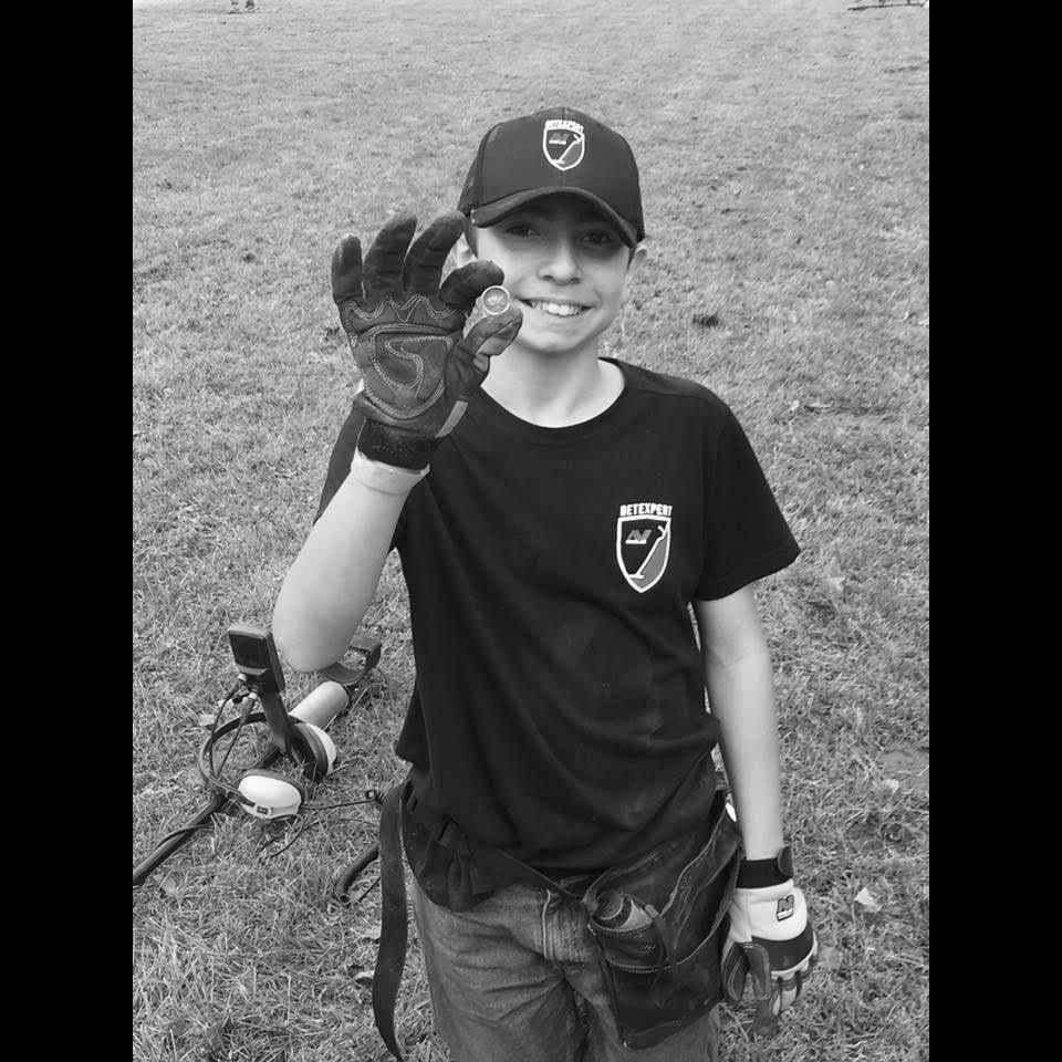 Black and White Image of Matty Tomaini of Digging with Matty Holding Up a Coin Find in His Hand with Minelab Gloves on and a Minelab Equinox Metal Detector on the Ground Behind Him and a Grassy Field in the Background