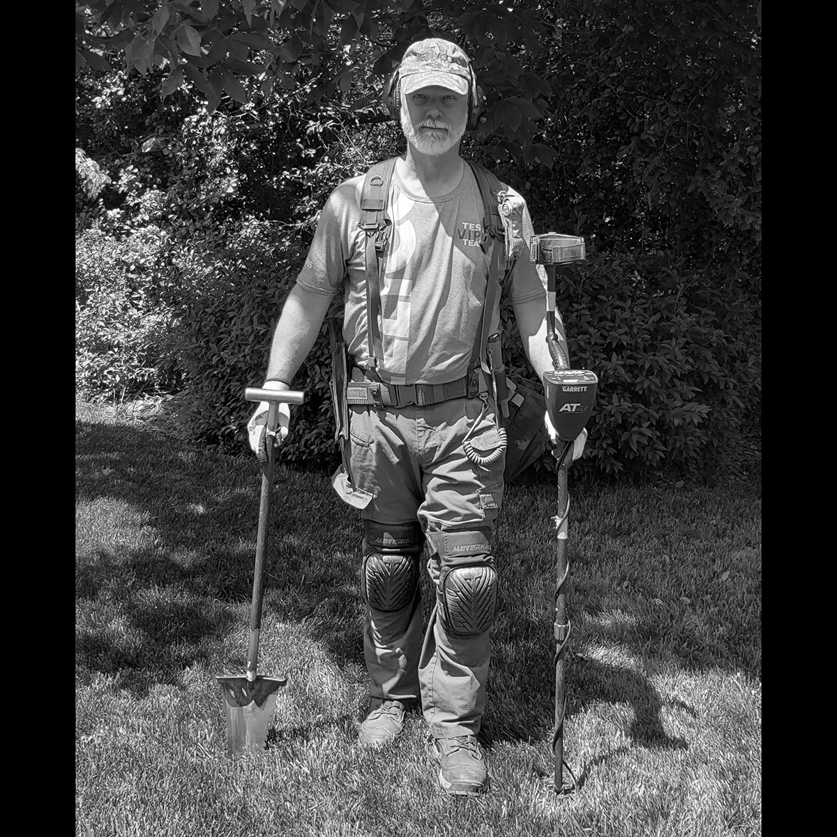 Black and White Image of Eric Reed of Reawakening History Holding Two Metal Detectors Standing in Grassy Area with Leaves and Trees in the Background