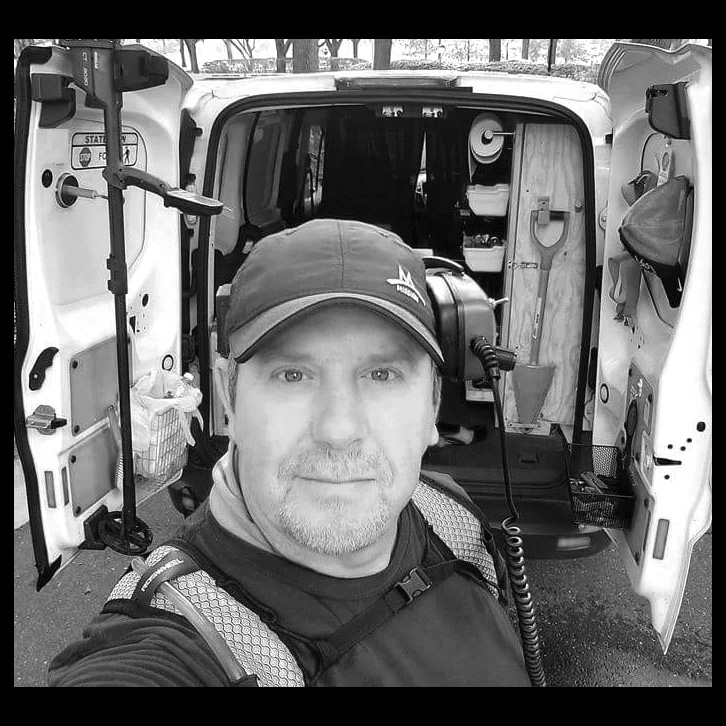 Black and White Image of Gary Penta of My Detecting Standing in Front of Van Filled with Detecting Gear Including Minelab CTX-3030 Shovel and Wearing Headphones