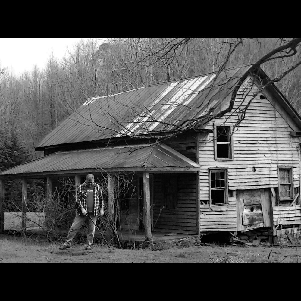 Black and White Image of Greg Pickens of Finding America Metal Detecting In Front of Old Rustic House with Bare Trees Around It and in the Background