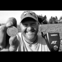 Black and White Image of The Hoover Boys' Kurt Franz Holding Coin Find Between Thumb and Forefinger with Garrett AT Max Metal Detector on His Shoulder