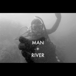 Black and White Image of Man Plus River Reaching Out Scuba Diving with Metal Detecting Gear and Foggy Water Filled with Bubbles Around Him