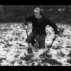 Black and White Image of Quarter Hoarder wearing MS-2 Headphones Holding Garrett AT Pro Metal Detector in One Hand and Grave Digger Tools Shovel in Other Hand in Snowy Field with Trees in Background
