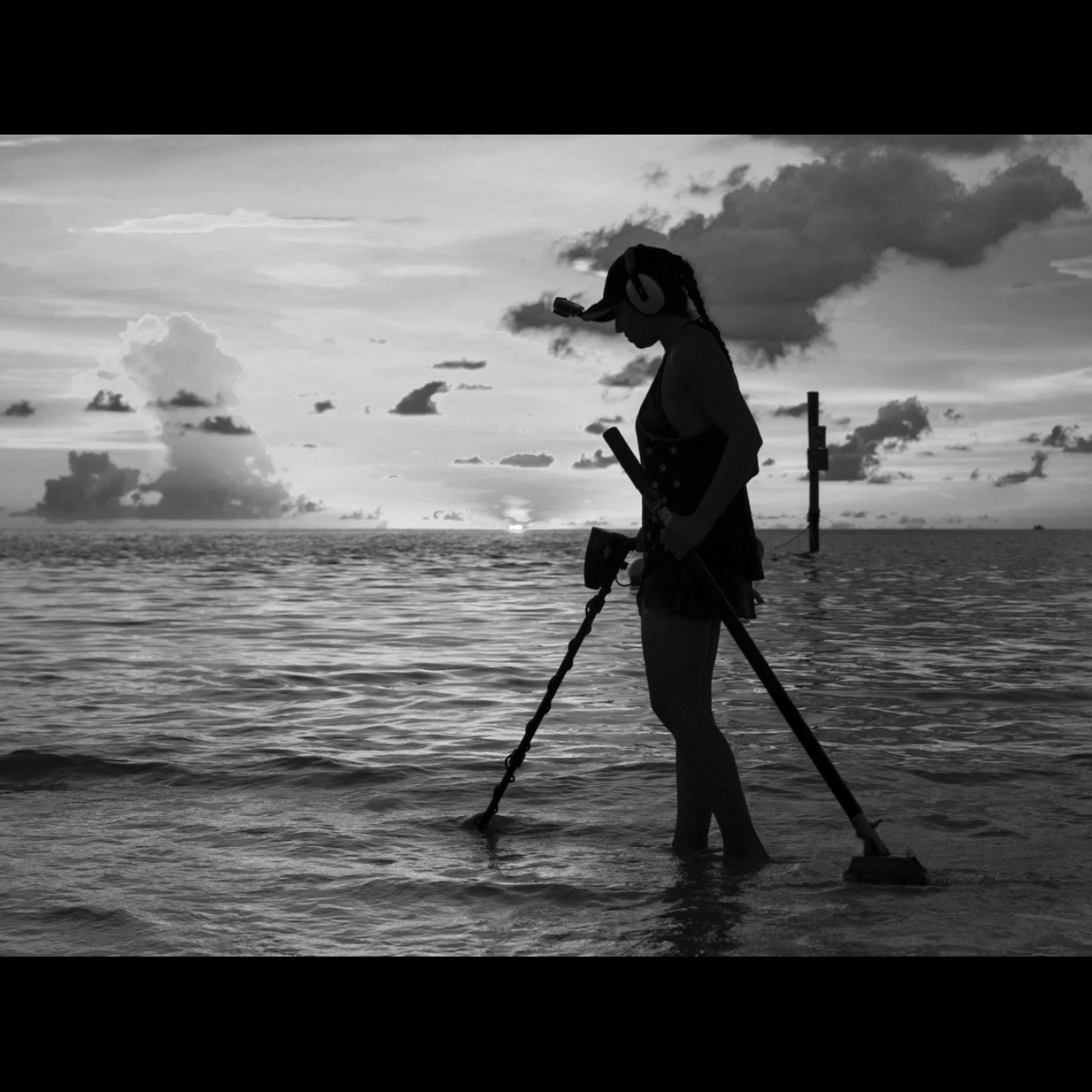 Silhouette of She Detector Water Hunting for Treasures at the beach with Garrett Metal Detector in Front of her and Sand Scoop Behind with Cloudy Sky in Background all in Black and White