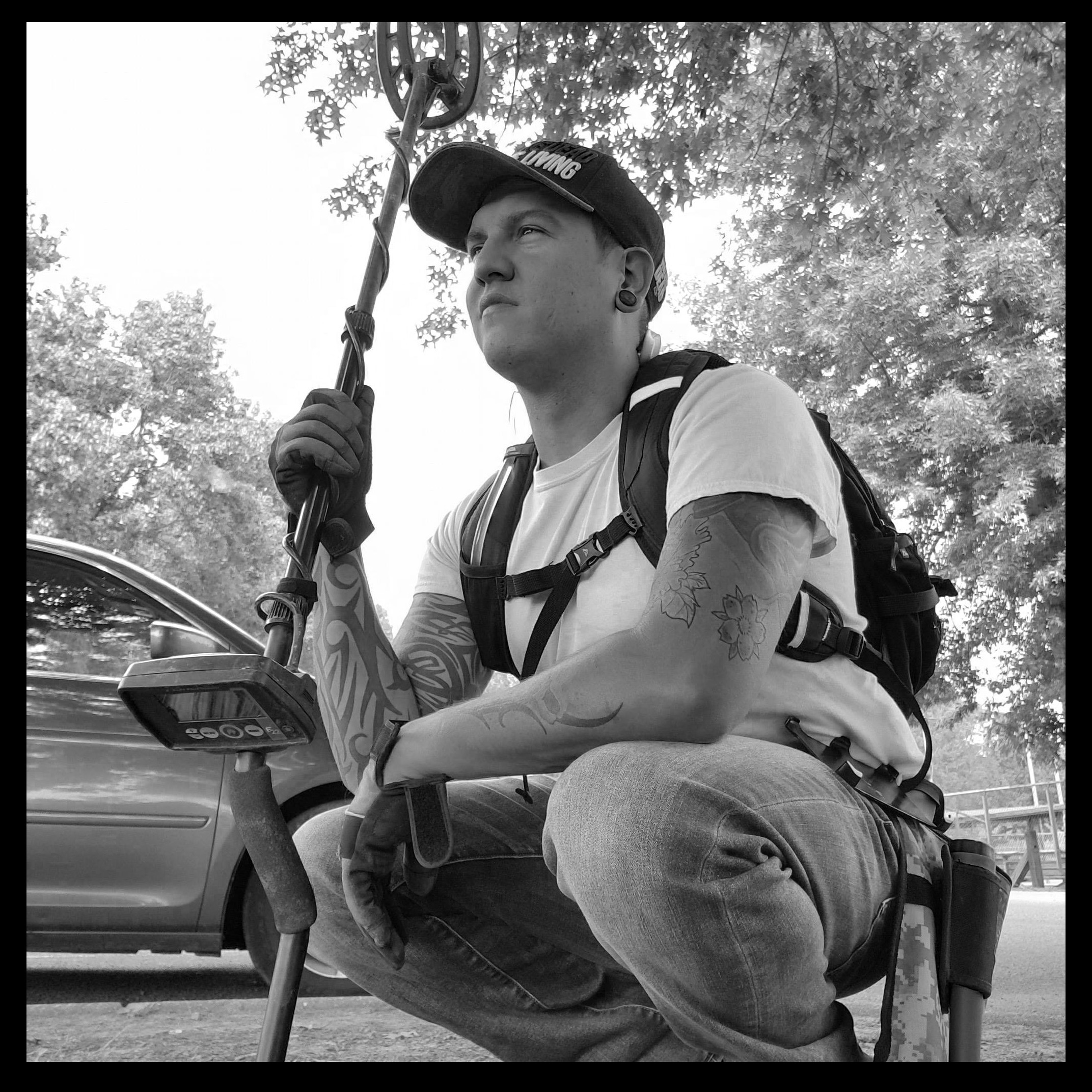 Tennessee Adventures Matt Ryan Holding Fisher Metal Detector with Trees and A Car in the Background all in Black and White