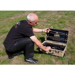 Man kneeling in grass opening carrying case of OKM GeoSeeker Water and Cavefinder 3025
