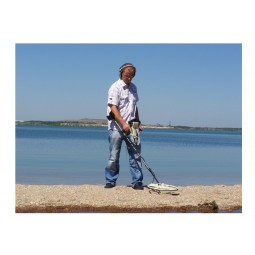 Man using OKM Black Hawk R3 Complete Kit Metal Detector on sand near water