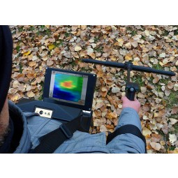 OKM eXp 6000 Professional Metal Detector being used in a leaf pile