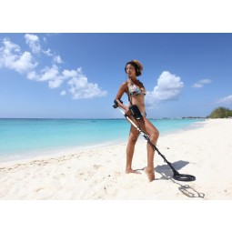 "Woman in a bathing suit holding Fisher 1280X Metal Detector with 8"" Search Coil on a white sand beach"