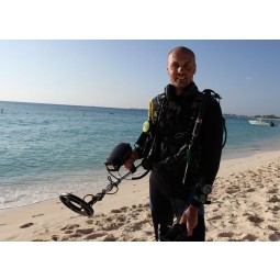 """Man holding Fisher CZ-21 Metal Detector with 8"""" Search Coil while walking on beach"""