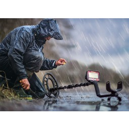 Man using Fisher F44 Weatherproof Metal Detector with Bonus Pack in rain