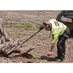 Police official using Garrett CSI Pro All Terrain Metal Detector and digging with shoval