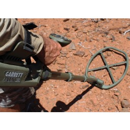Man's hand shown holding Garrett ATX Pro DeepSeeker metal detector on rocky soil