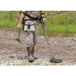 Lower half of man using Garrett ATX Extreme PI Metal Detector in rocks near creek