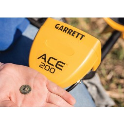 Hand with treasure find and Garrett ACE 200 metal detector