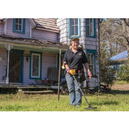 Woman in a black shirt using a Garrett ACE 400 metal detector in front of a pink house