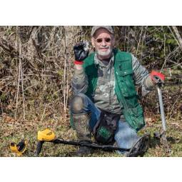 Man in a green vest holding a coin he found using Garrett ACE 400 metal detector