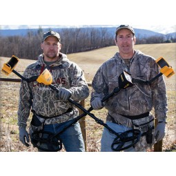 Two men in a field wearing camouflage crossing two Garrett ACE 400 metal detectors
