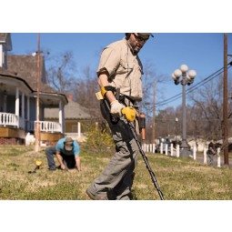 Man in sunglasses and hat searching a front yard with Garrett ACE 400 metal detector