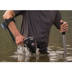 Midsection of a man in waist deep water using a Garrett AT Max Metal Detector