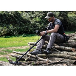 Man sitting on logs while holding Nokta Makro ANFIBIO Multi Metal Detector