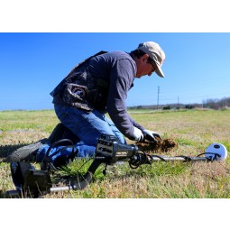 Man kneeling in grass using Nokta Makro AU Gold Finder Metal Detector