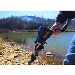 Person holding shaft of Nokta Makro AU Gold Finder Metal Detector near a shallow river