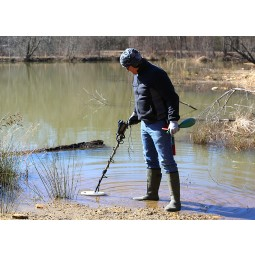 Man wearing waterproof boots using Nokta Makro AU Gold Finder Metal Detector in shallow water