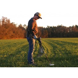 Man wearing brown hat using Nokta Makro AU Gold Finder Metal Detector in flat grassy field