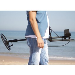 Man holding Nokta Makro Deephunter 3D Pro Package Metal Detector on beach near ocean