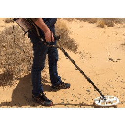 Man using Nokta Makro FORS Gold Metal Detector Pro Package with search coil in desert sand