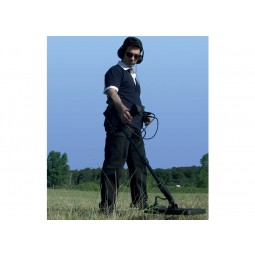 Looking up from the ground at a man in all black using a  Nokta Makro Jeohunter 3D Basic System Metal Detector