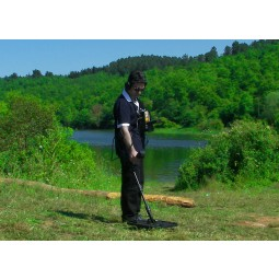 Man standing on grass near riverbank holding  Nokta Makro Jeohunter 3D Basic System Metal Detector