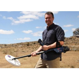 Man holding Minelab GPZ 7000 Metal Detector in grassy plains