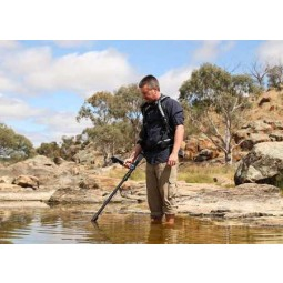 Man standing in shallow water using Minelab GPZ 7000 Metal Detector
