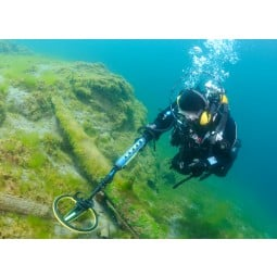 Scuba diver using Minelab Excalibur II Metal Detector underwater near a wreck