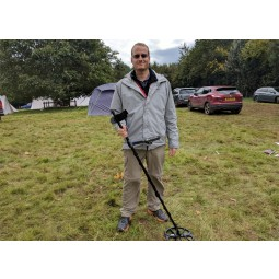Minelab Equinox 600 Metal Detector being held by a man in a grassy parking lot