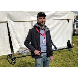 Minelab Equinox 600 Metal Detector being held by man in front of white tent