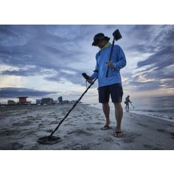 Man using Minelab Equinox 800 Metal Detector on a beach