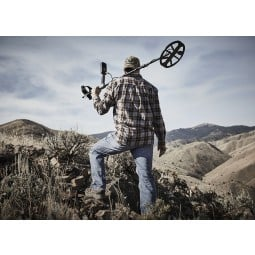 Man carrying Minelab Equinox 800 Metal Detector walking over mountains