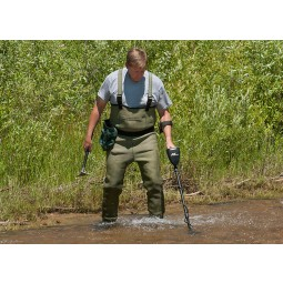 Man wearing weighters using Garrett AT Gold metal detector in fresh water stream
