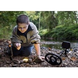 Small boy looking at treasure found with Teknetics Digitek Metal Detector with Bonus Pack near a shallow river