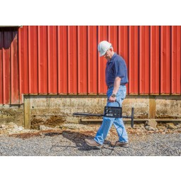 Man in a hardhat carrying White's TM 808 Specialty Metal Detector over concrete near steel building