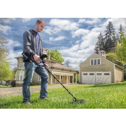 Young man using White's Spectra V3i Metal Detector in residential area backyard