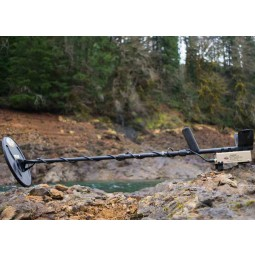 White's TDI SL Metal Detector Special Edition rest on a rock near a river