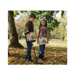 Young boy and girl using White's XVenture Kit Metal Detector under a tree
