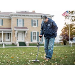 Man wearing headphones using White's MX7 Metal Detector in a grassy yard with American flag flying in background