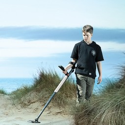 Teenage boy using Minelab GO-FIND 11 Metal Detector on the beach