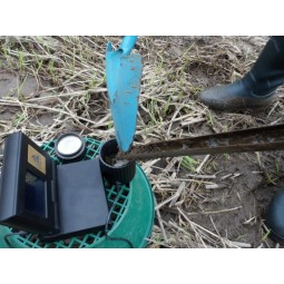 Shovel dropping ground sample into measuring cup that is part of OKM Gold Labor Au 79 Metal Detector
